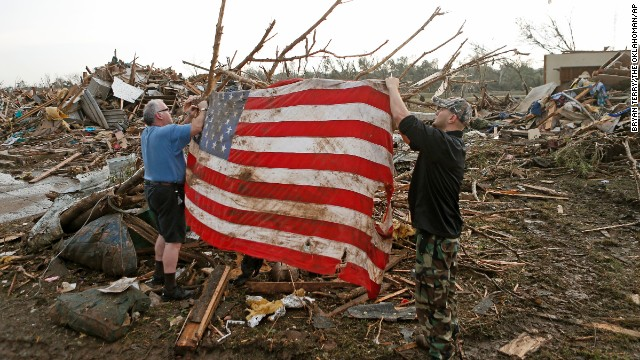 Clark Gardner, at left, and another man, place an American flag on debris in a neighborhood off of Telephone Road in Moore, Oklahoma, after the tornado moved through the area on Monday, May 20, 2013. AP Photo/ The Oklahoman, Bryan Terry - photographer.