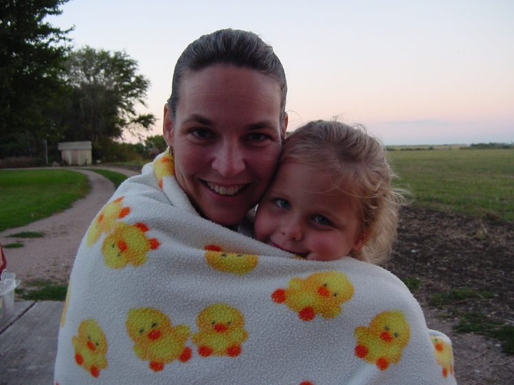 Em and me back in 2004 wrapped in a duck blanket on a chilly night by a bonfire.