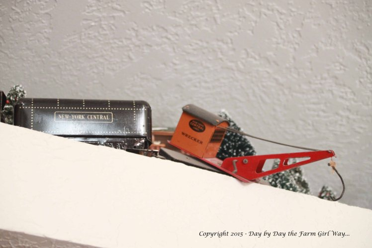 The crane car hangs off the edge of the ledge.