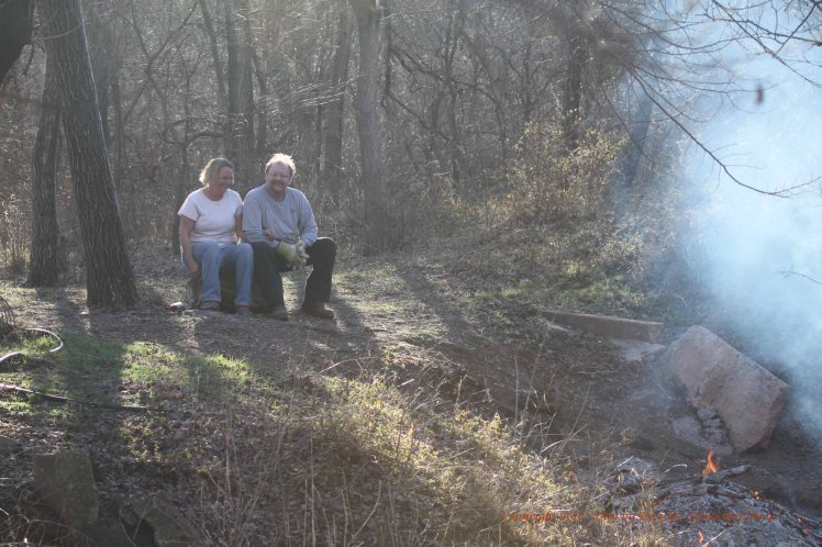 Lisa and her friend Doug enjoy the warmth of the fire and the beauty of the woodlands.